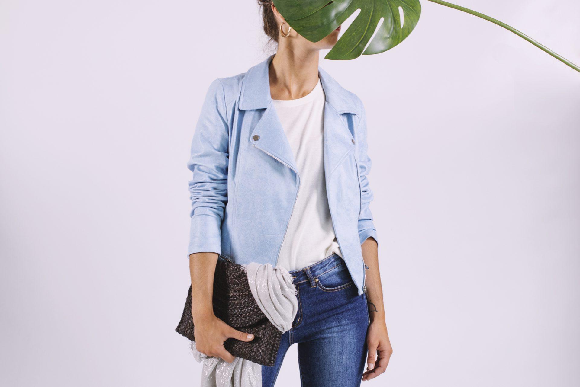 Baqueros y camiseta blanca con chupa azul y un bolso oscuro