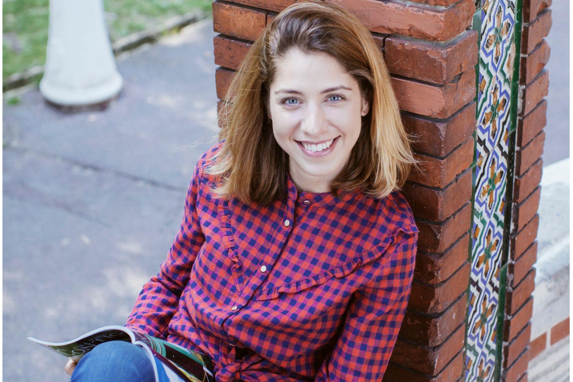Mujer rubia con ojos azules vistiendo camisa de cuadros azul y rojo