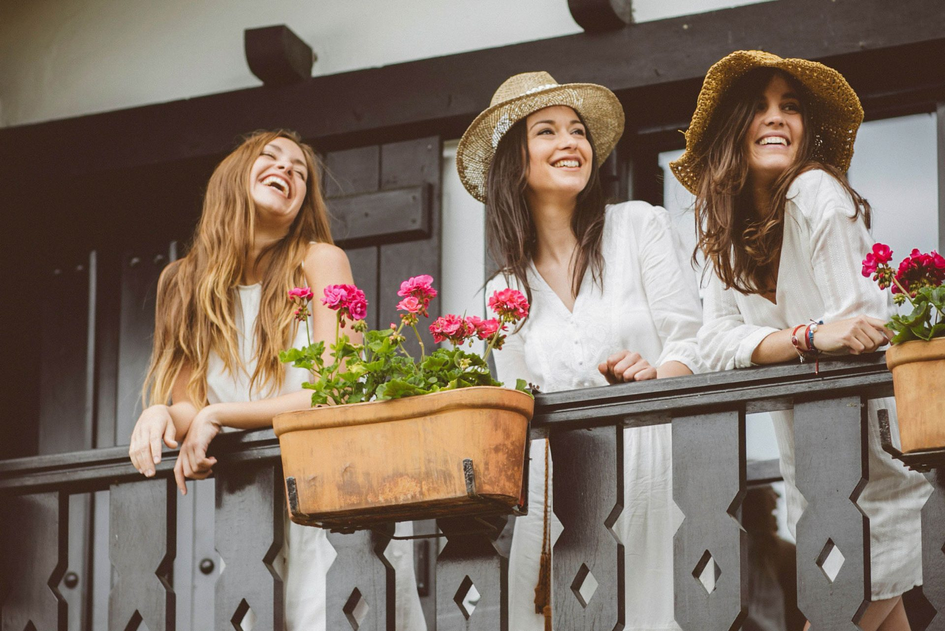 chicas felices con vestido blanco en un balcón