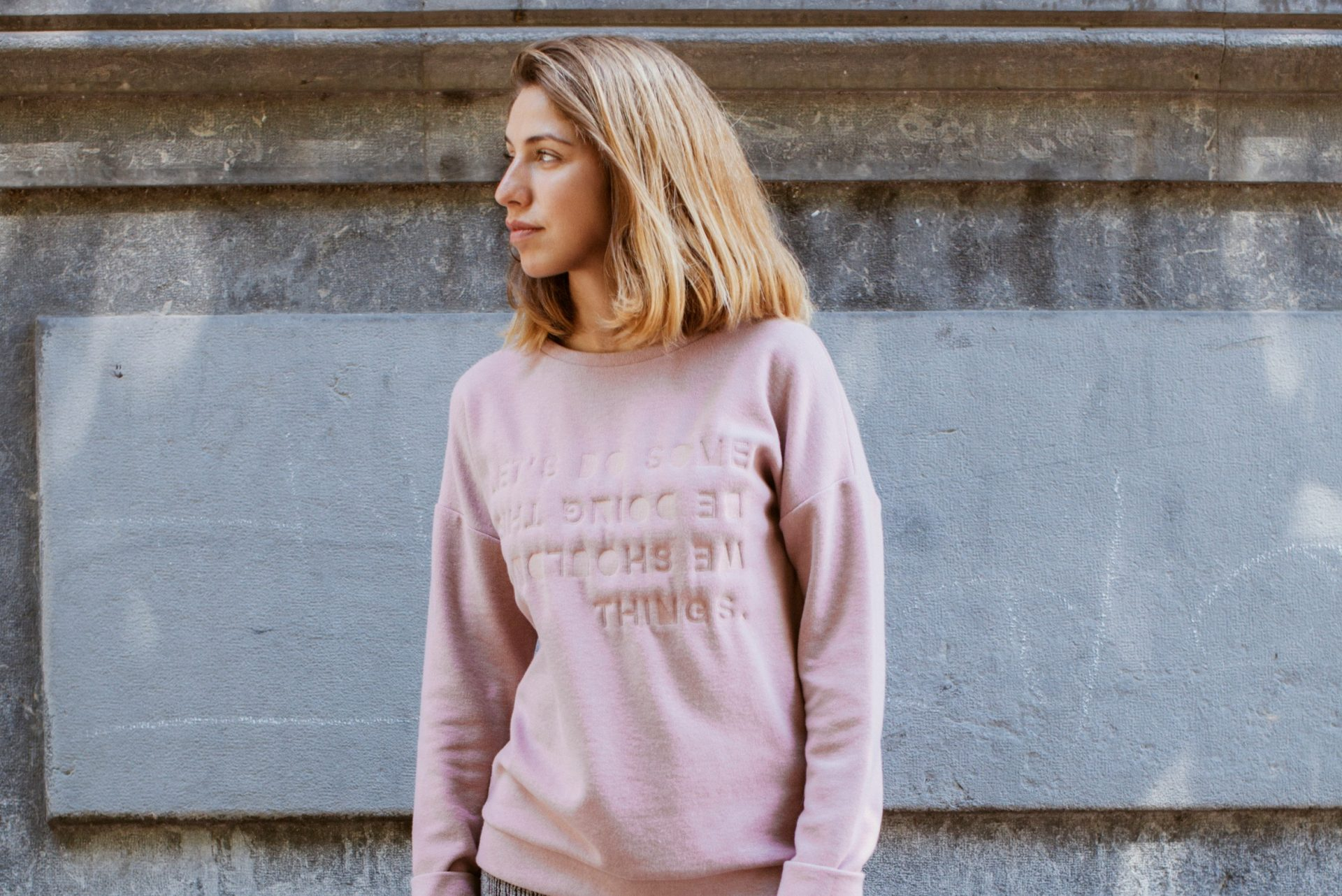 mujer rubia con jersey rosa