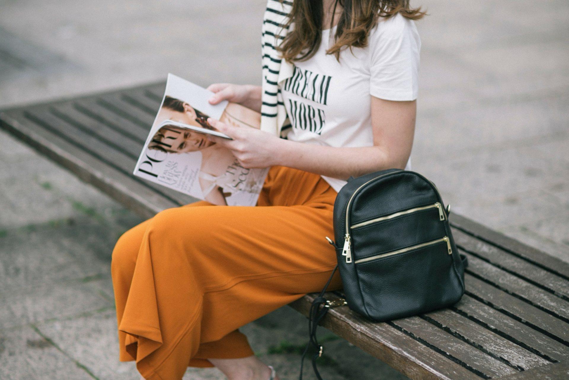 Pantalón flojo anaranjado con camiseta de mensaje y mochila negra