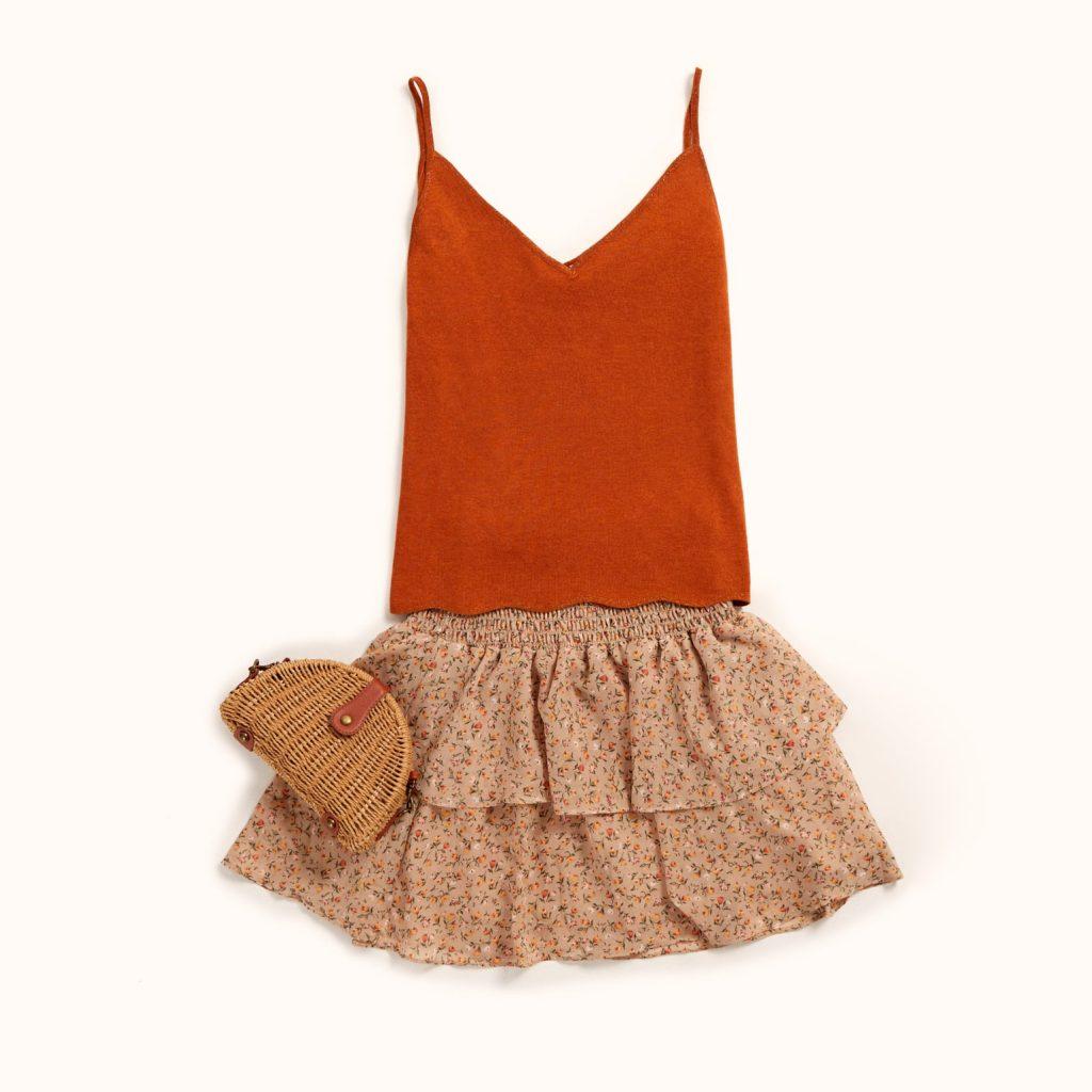 top de alças cor terra combinado com uma saia ligeira de folhos de padrão floral.