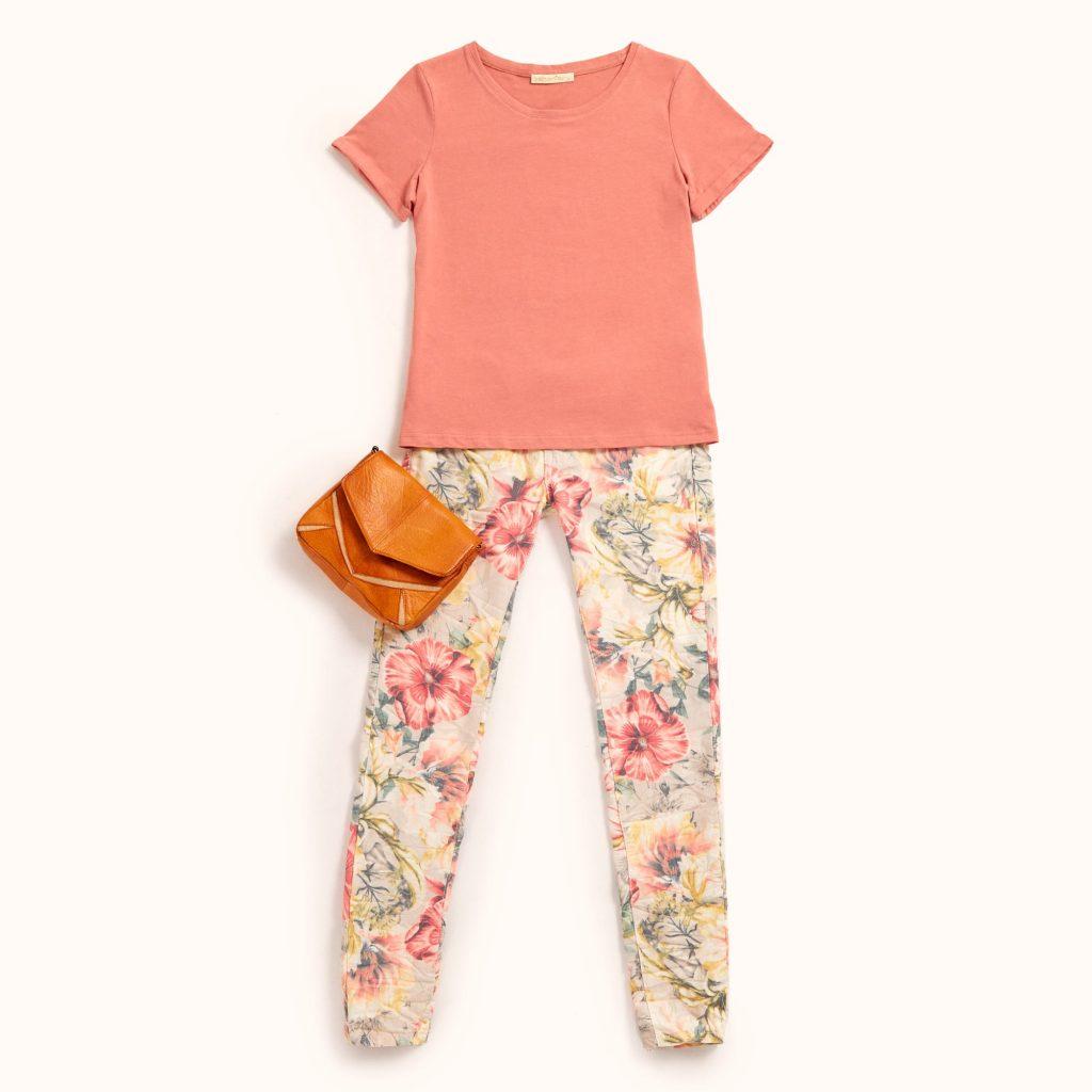 t-shirt básica em tom salmão conjugada com uns jeans de estampado floral maxi